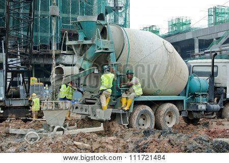 A concrete bucket receiving concrete from concrete truck