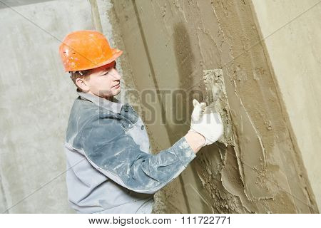 Construction worker plasterer with trowel plastering a wall