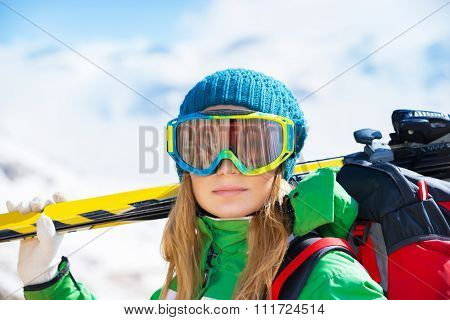 Portrait of healthy woman wearing sportive mask and holding ski in hands, spending winter holidays in snowy mountains