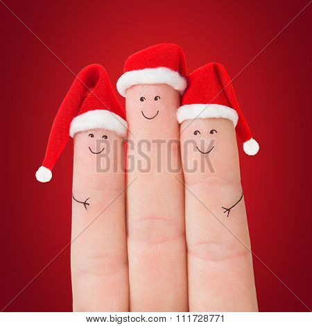 Three Fingers Faces In Christmas Santa Hats Against Red Background