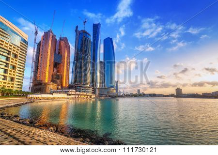 ABU DHABI, UAE - MARCH 27, 2014: Sunrise at Etihad Towers in Abu Dhabi, UAE. Five towers complex with 74 floors is the third tallest building in Abu Dhabi.