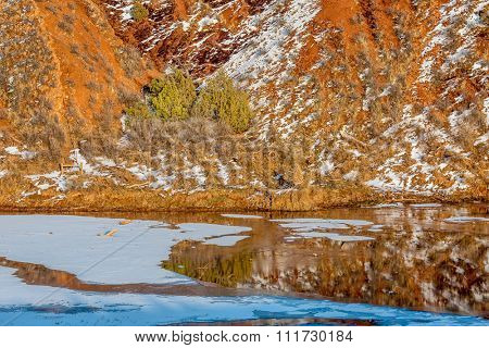 water, snow, ice and red hills  - winter scenery in Red Mountain Open Space near Fort Collins, Colorado