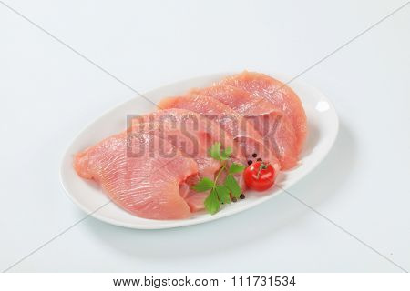 Raw turkey breast escalopes on plate