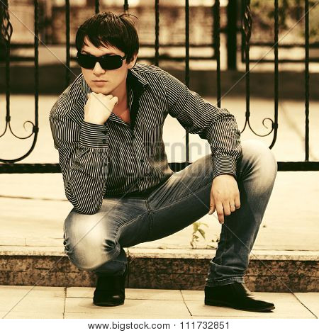 Young handsome man in sunglasses sitting at the cast iron fence