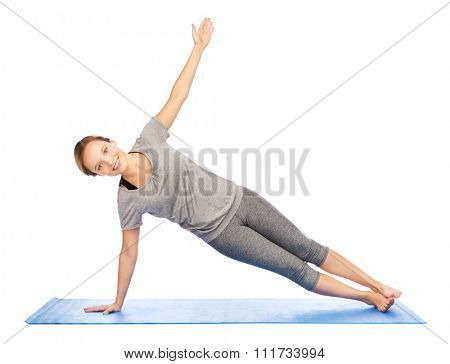 fitness, sport, people and healthy lifestyle concept - woman making yoga in side plank pose on mat