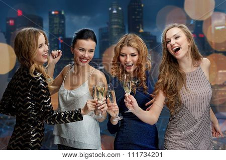 celebration, friends, bachelorette party, nightlife and holidays concept - happy women clinking champagne glasses and dancing over night city lights background