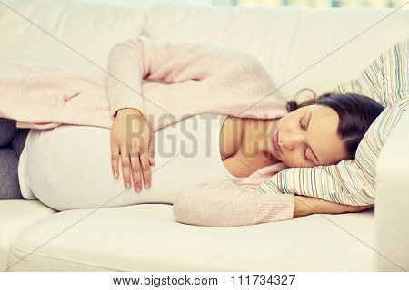 pregnancy, rest, people and expectation concept - happy pregnant woman sleeping on sofa at home