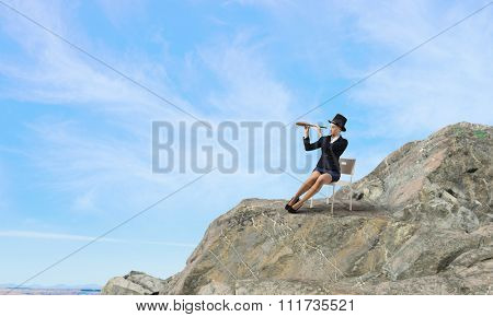 Pretty girl wearing retro hat siting on chair and looking in spyglass