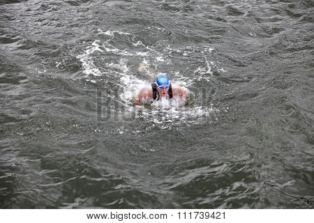 iron man - dynamic and fit swimmer in cap and wetsuit breathing  performing butterfly stroke in dark sea water