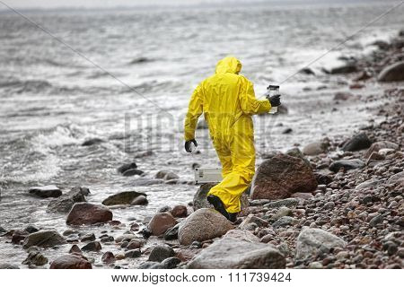 scientist in protective suit with plastic container walking in on rocky beach - back view