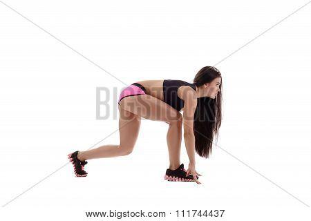Beautiful female sprinter posing on starting block