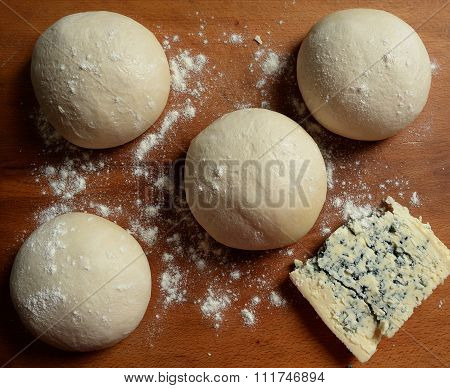 Small balls of fresh homemade pizza dough on floured wooden board