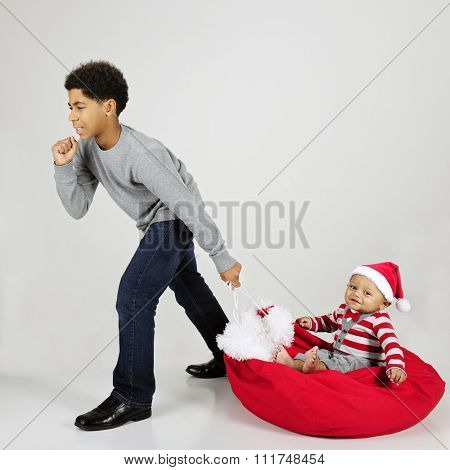 An elementary boy struggling to give his baby brother a ride across the floor on Santa's sack.  On a gray background.