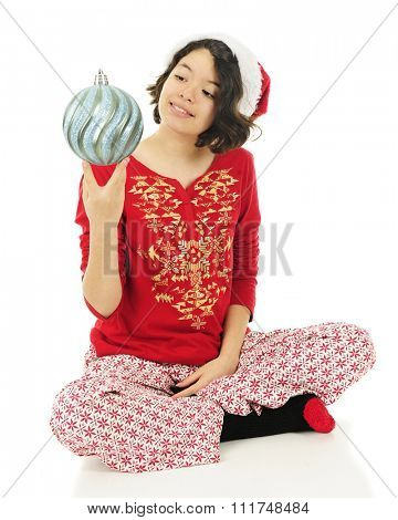 A pretty Hispanic girl in her pajamas admiring her favorite Christmas bulb.  On a white background.