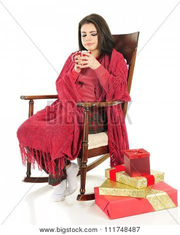A beautiful teen girl sipping hot chocolate while snuggled up in a red blanket, Christmas gifts near her rocking chair.  On a white background.