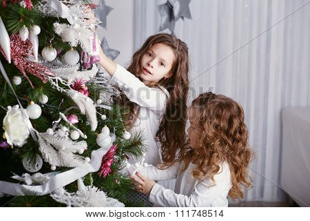 Two Little Sisters Decorating Christmas Tree With Toys And Balls.