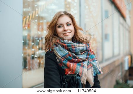 Cute Woman In Warm Clothes On The Background Of The Store With Lights