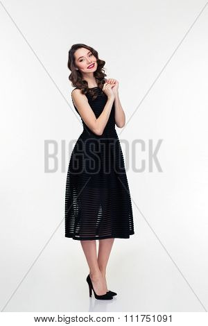Full length of cheerful attractive retro styled female in black dress standing over white background