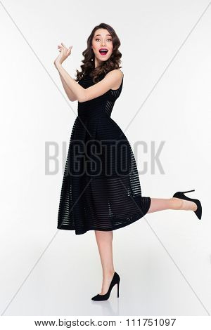 Cheerful beautiful woman with bright makeup in retro style throwing something with both hands to the side isolated over white background