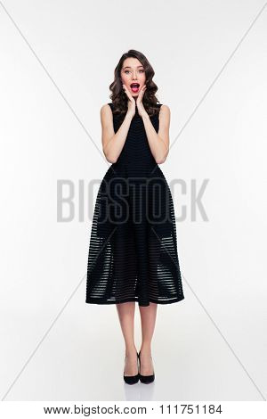 Full length of amazed happy young woman with makeup in retro style in black dress standing over white background