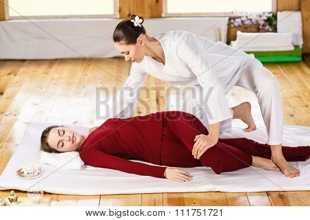 Woman getting thai stretching massage