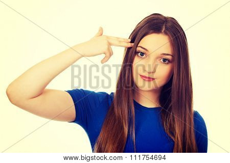 Young woman with hand to head in the shape of gun.