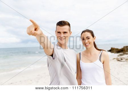 Young couple of runners  in sports wear standing together on beach and poiting at the distance