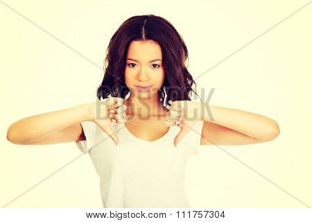 Young unhappy african woman showing thumbs down.