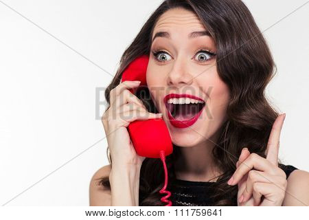 Excited lovely cute young woman in retro style talking on telephone and pointing away over white background