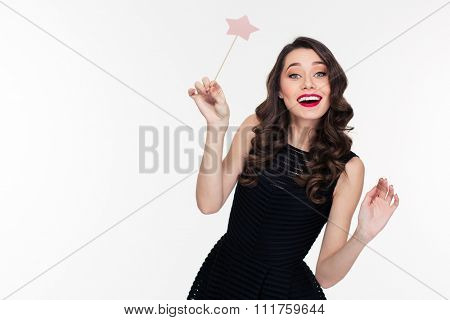 Cheerful beautiful curly young woman with retro hairstyle in black dress posing with magic wand over white background