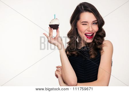 Attractive playful retro styled curly young woman holding birthday cupcake with candle and winking over white background