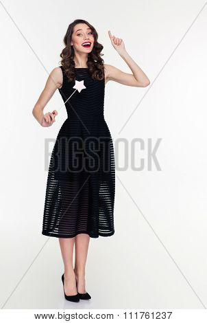 Full length portrait of inspired beautiful young retro styled woman making a wish and using magic wand isolated over white background