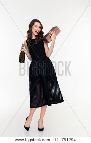 Full length of attractive flirty retro styled young woman in black dress and shoes holding bottle of champagne and gift and winking over white background