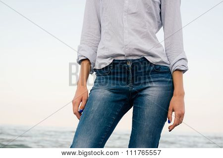Woman In A Striped Shirt And Blue Jeans Standing On Sea Background