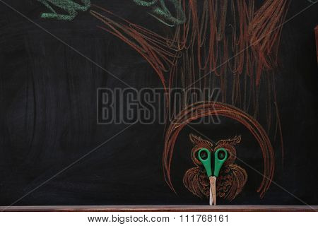 Concept of owl in hollow tree with scissors and chalk on black background