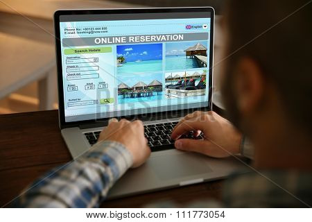 Man using laptop to book hotel online