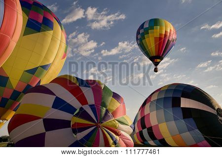 Hot Air Balloon Floating Over Other Inflating Balloons