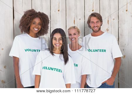 Happy group of volunteers against wooden background