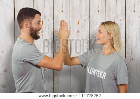 Smiling volunteer doing high five in office against wooden background