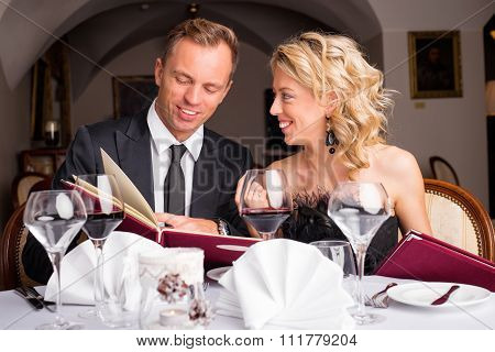 Couple at restaurant choosing what to eat from menu