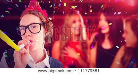 Geeky hipster wearing a party hat wig blowing party horn against pretty friends drinking cocktails together