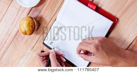 New years resolution list against overhead of feminine hands writing on agenda