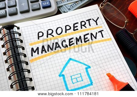 Notebook with property management sign on a table.