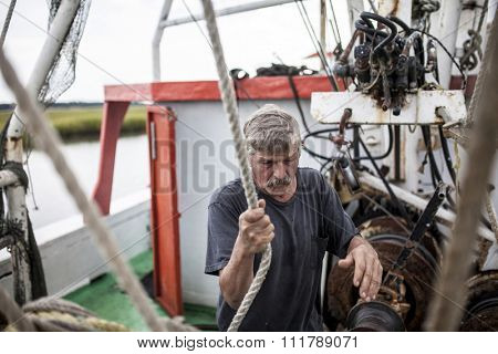 BEAUFORT, SOUTH CAROLINA-OCTOBER 16, 2015: Unidentified worker hauls a net on a fishing vessel off the coast of Beaufort, South Carolina