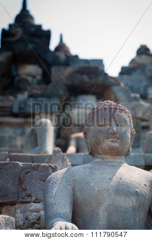 Sitting and smiling Buddha in stone at Borobudur