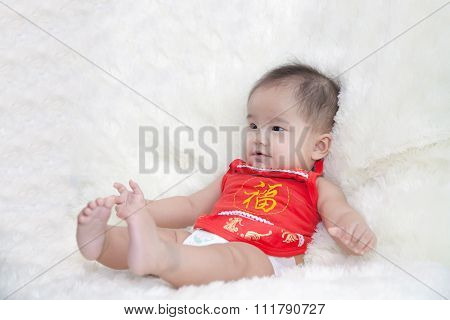 Cute Five Months Asian Baby Smiling In Red Cheongsam., On Bright Soft Carpet., Chinese Character Is