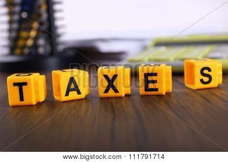Alphabet TAXES on wooden table