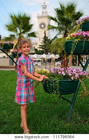 Smiling girl standing near flowerpot with flowers on lawn of summer day