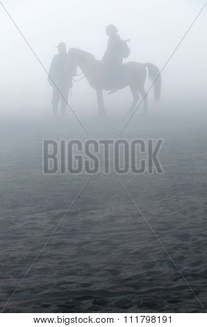 Silhouette of people and horses in fog or mist