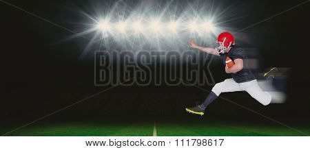 American football player jumping with the ball against rugby stadium